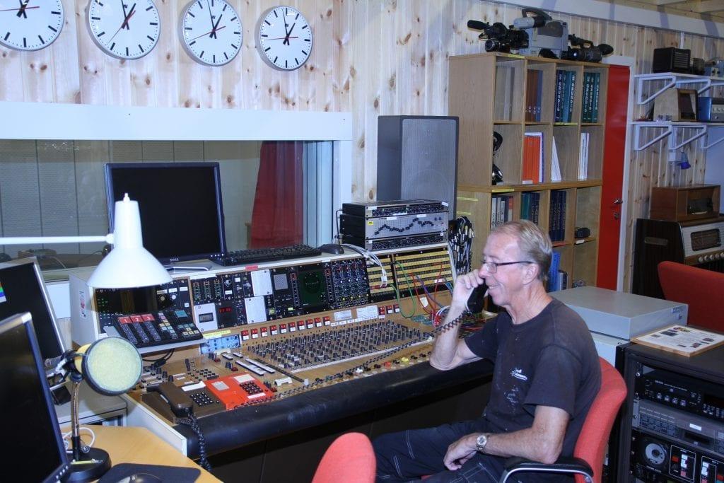 Museumsbestyrer Jan Erik Steen der han trives best, blant radio- og fjernsynsapparater og studioutstyr på museet i Sjøbygda. Her har han full kontroll over radiosendingen fra NRK-studioet som kom fra Lø i Steinkjer.