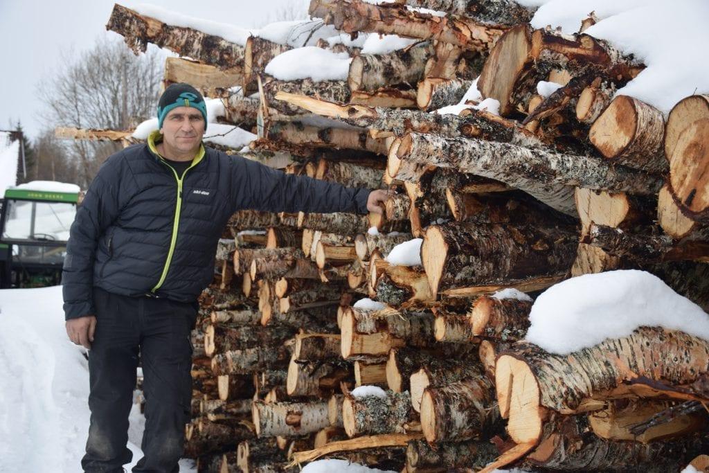 Flemming Lunden står ved vedstrangene som snart skal bli ved