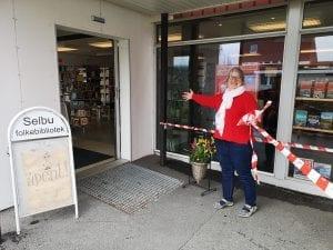 - Endelig kan jeg ønske publikum hjertelig velkommen igjen, sier Oddbjørg Øiberg mens hun fjerner «korona-tapen» som har stått foran biblioteket i over en måned.