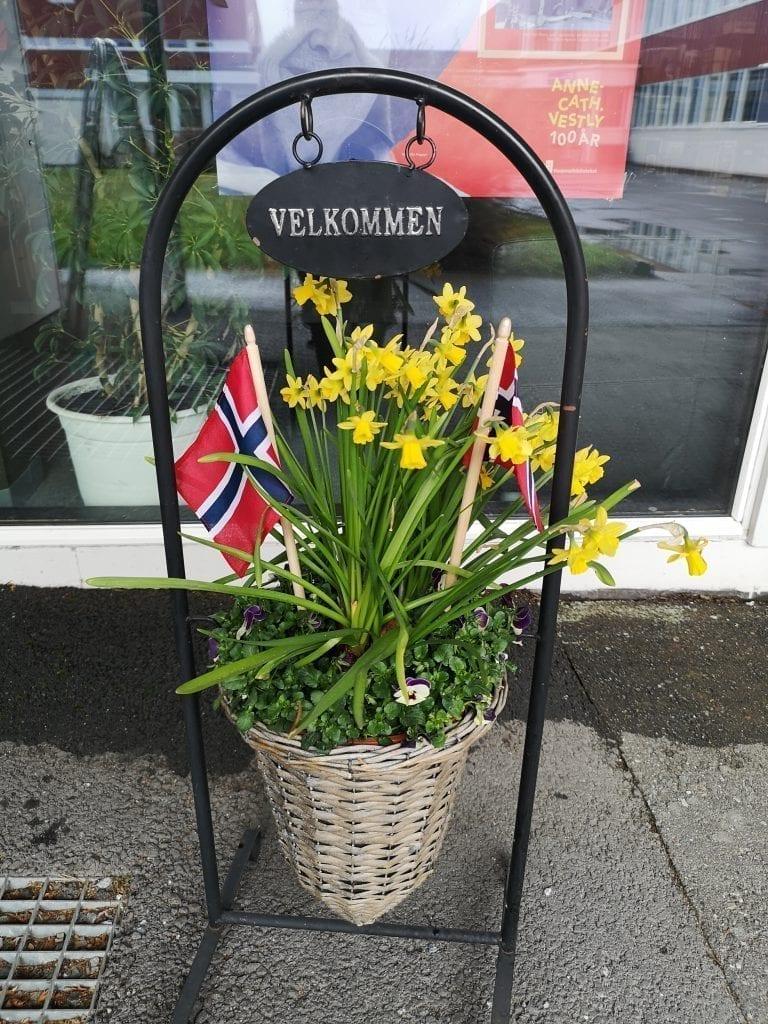 Publikum blir møtt velkommen med blomster og norske flagg