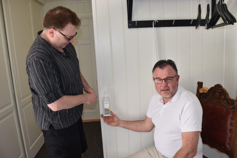 Hans Sigvard Hanssen og Birger Aftret demonstrerer her bruk av Antibac som er montert på holder i Birgers hjem i Vikvarvet