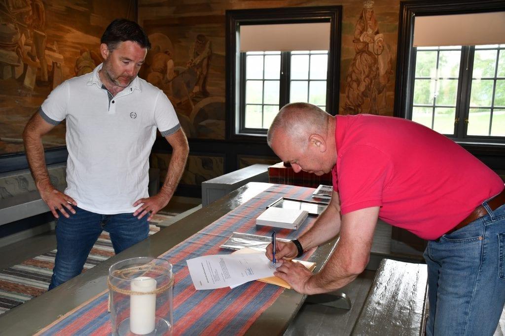 Bildetekst Ordfører Ole Morten Balstad og Styreleder i Husfliden AS, Mikal Langseth, signerer avtalen om overlevering av gamle strikkeoppskrifter og medaljer på Selbu Bygdemuseum.