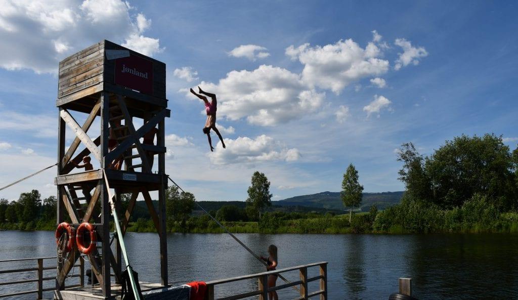 Steffen Strand (18) fra Trondheim tar backflip fra stupetårnet ved Garbergselva.