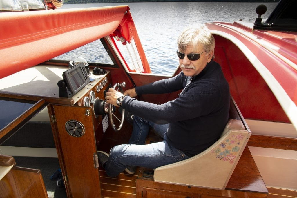 Jan Ove Evjemo sitter foran roret på båten sin, på Selbusjøen.