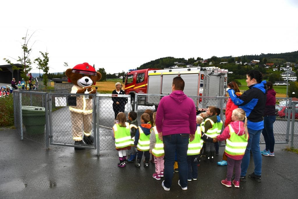 Brannbamsen Bjørnis tar seg tid til å hilse på alle barna i Kvellohaugen barnehagen.