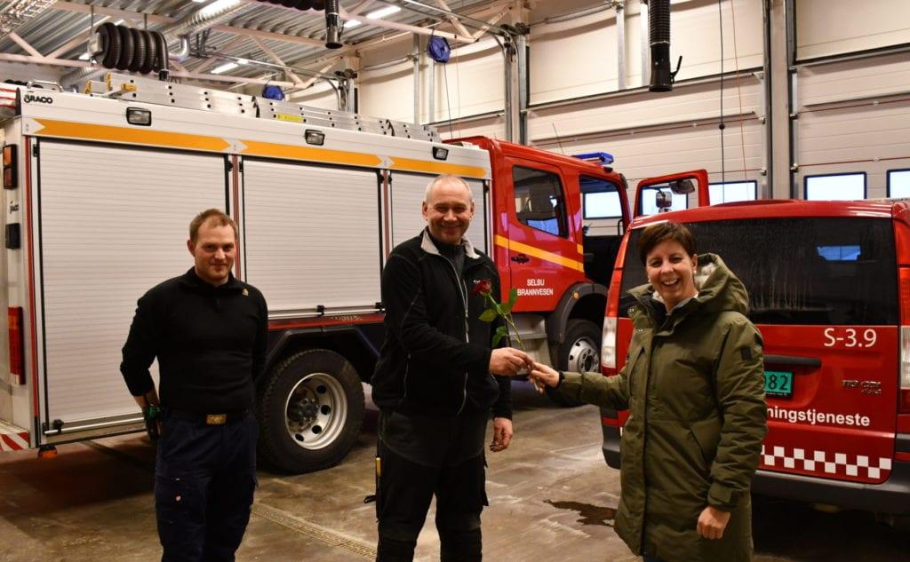 Hanne Sundal Kulseth gir ukens rose til Selbu brann- og redningstjeneste for formidabel jobb i slukking av brannen i hjemmet på Åsbaret i Selbu. Her med utrykningsleder Frode Welve (t.h) og stasjonsmester Per Erik Eidem.